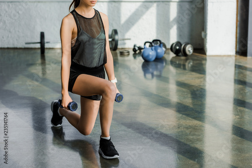 Fotografia  cropped view of sportswoman doing lunge exercise with dumbbells at sports center