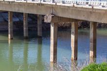 Concrete Piles On A Bridge Over The River