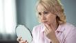 Leinwandbild Motiv Unhappy senior female looking at sagging skin face in mirror, old age appearance