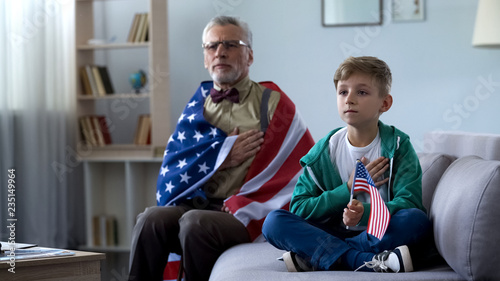 Photo Patriotic old man holding American flag, listening national anthem with grandson