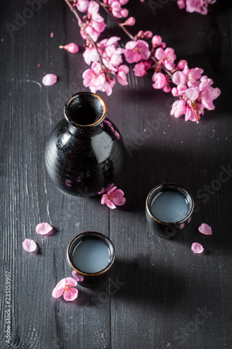 Strong sake with blooming flowers on black table