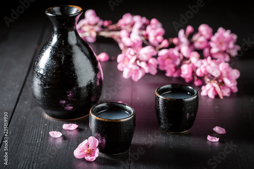 Unfiltered strong sake in black ceramics on dark table