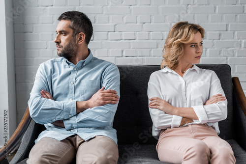 mad couple sitting on couch after quarrel and looking away Wallpaper Mural