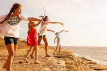 Teens Throwing Stones Over Cliff Edge At Seaside