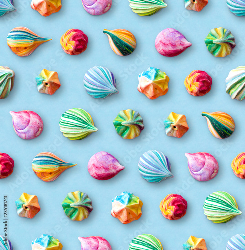 Seamless pattern of multicolored meringues. Colorful little meringue cakes on a blue pastel background.