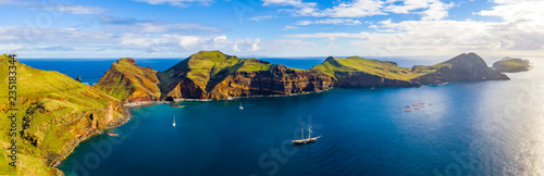 Photo Stands Night blue Aerial tropical island view in the middle of the ocean with rocky cliffs and green fields