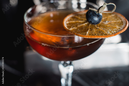 Foto The Boulevardier Cocktail with orange chips on top. On a bar desk