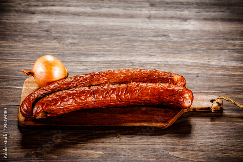 Raw sausages with onion on cutting board