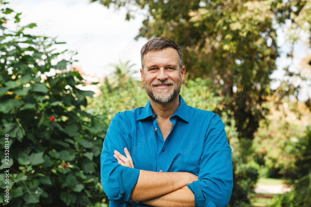 Fototapeta Portrait of Senior man caucasian smiling and looking at camera, outside in park.