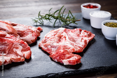 Raw beefsteaks on black stone on wooden background