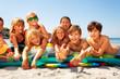 Happy friends sunbathing on sandy beach in summer