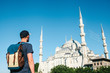 A tourist with a backpack admires the Blue Mosque in Istanbul in Turkey. Sightseeing.