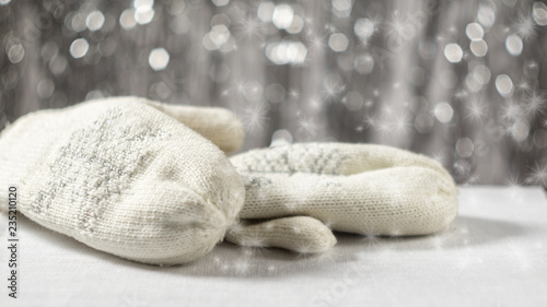 Fotografie, Obraz  Knitted white mittens on a brilliant background