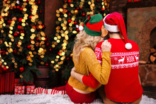 Couple In Love, Man Male Husband And Woman Female Wife In Santa Elf Hats And Warm Red Sweaters Hugging At Home Near Christmas Tree Anf Fireplace Before Night Of Christmas Eve And Happy New Year 2019.