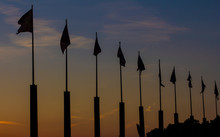 Silhouette Of Flagpoles At Sun...