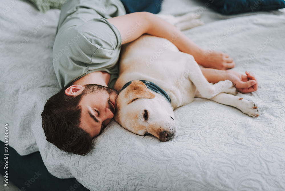 Fototapeta Pleasant young man enjoying his sleep while embracing his dog