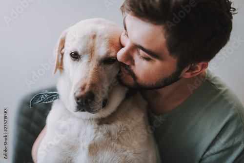 Obraz Close up of a bearded man kissing his dog while enjoying rest together - fototapety do salonu