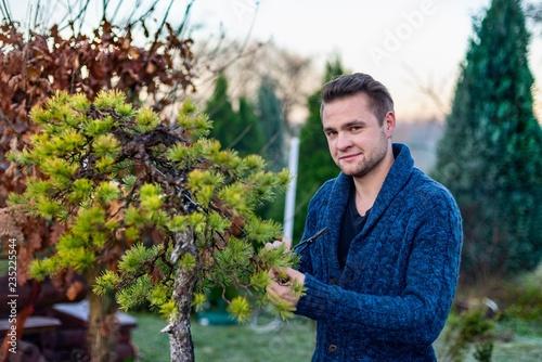 Man pruning japanese bonsai tree