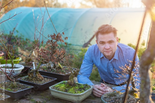 Young man in his bonsai tree farm.