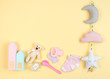 canvas print picture - Baby girl accessories and toys on yellow background with copy space