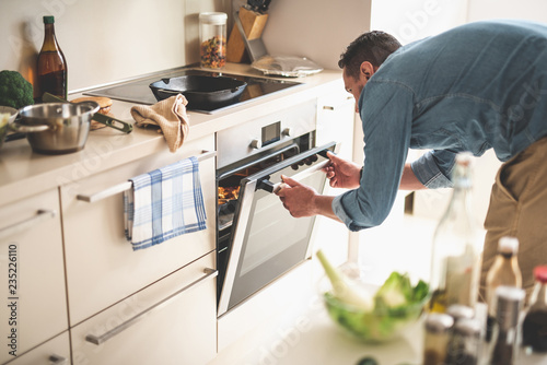 Portrait of gentleman in denim shirt closing door of oven while looking at frying pan with beef steak
