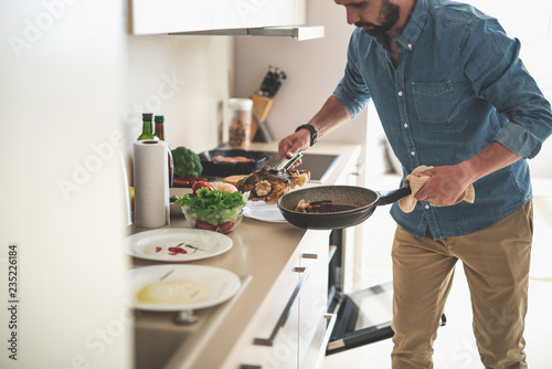 Stampa su Tela Cropped portrait of gentleman in denim shirt holding frying pan and tongs with b