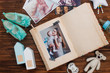 canvas print picture - Open album with picture near accessories on wooden background with copy space