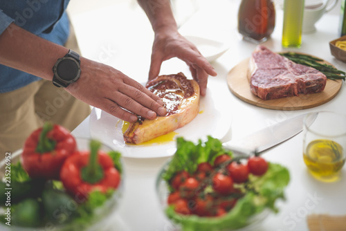 Close up of male hands greasing raw beef steak with olive oil. Fresh vegetables, knife and cutting board on blurred background
