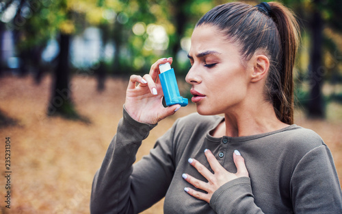 Photo Young woman treating asthma with inhaler