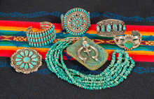 Collection Of Native American Jewelry On A Colorful Textile Background. Turquoise And Sterling Silver Necklace, Bracelets And Pendants.