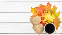 Cup Of Coffee With Two Burlap Hearts And Autumn Leaves On White Wooden Table.Top View. Space For Text.