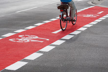 Unrecognizable Cyclist Cycling And Crossing Street On Red Bike Lane