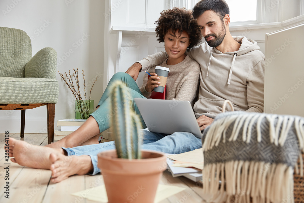 Fototapety, obrazy: Lovely family couple cuddle together, dressed casually, enjoy domestic atmosphere, synchronize data on laptop computer, work on family business project, drink hot beverage, cactus in foreground