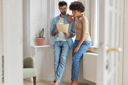 Fotografía  Family couple look at bill, plan their budget and count expenses, dressed in jeans, drink takeaway coffee, pose in modern apartment near window