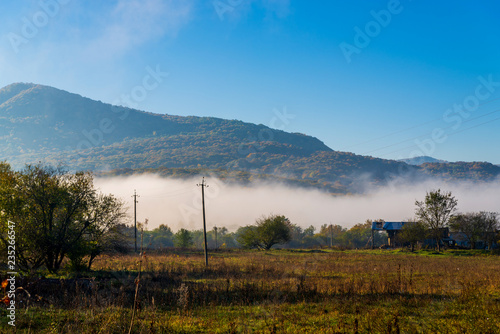 Beautiful landscape in the mountains at sunrise. View of foggy hills covered by forest