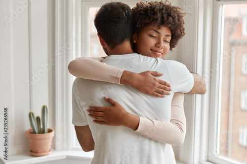 Canvas Print Pleased dark skinned young woman gives warm hug to her boyfriend, being pleased, pose near window, have romantic relationship, stand in cozy room