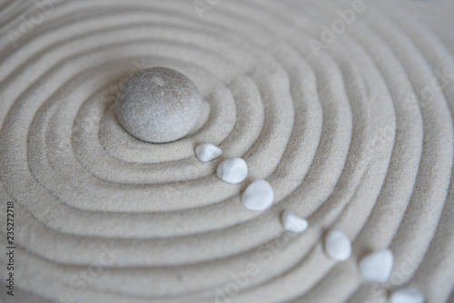 Foto op Plexiglas Stenen in het Zand Gray zen stones on the sand with wave drawings. Concept of harmony, balance and meditation, spa, massage, relax