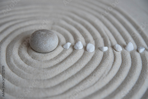 Papiers peints Zen pierres a sable Gray zen stones on the sand with wave drawings. Concept of harmony, balance and meditation, spa, massage, relax