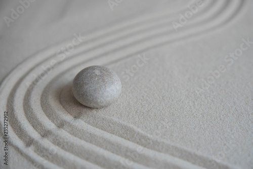 Gray zen stones on the sand with wave drawings. Concept of harmony, balance and meditation, spa, massage, relax