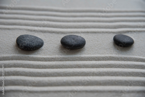 Deurstickers Stenen in het Zand Gray zen stones on the sand with wave drawings. Concept of harmony, balance and meditation, spa, massage, relax
