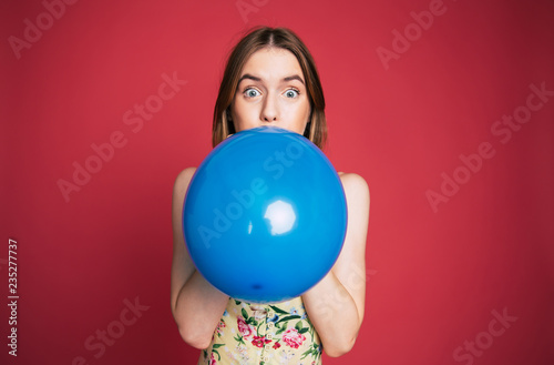 Fototapeta Young emotional cute blonde woman is blowing blue balloon on pink background and