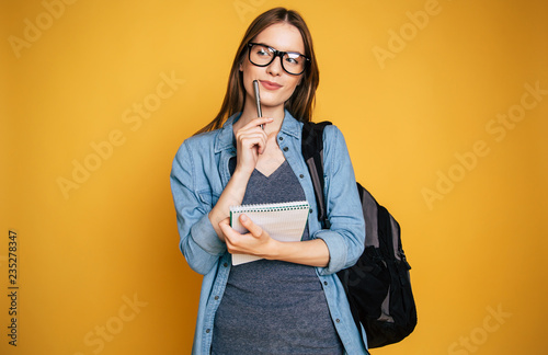 Tablou Canvas Happy and excited cute young student girl portrait in glasses with backpack isol