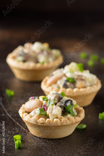 Russian salad with meat and beans in tartlet. With potatoes, egg, cucumber, onion, mushrooms and mayonnaise. Delicious appetizer for wine buffet