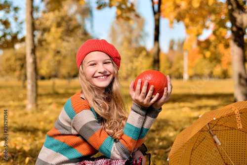 Autumn portrait of happy girl in red hat and sweater Canvas Print
