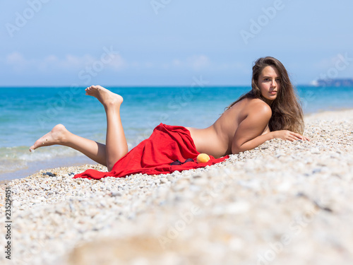 Poster Akt Female person sunbathes lying on pebble
