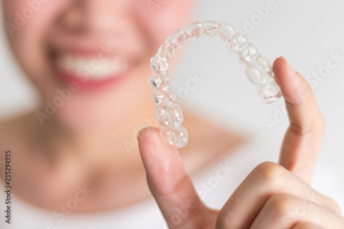 Fotografia  A smiling woman holding invisalign or invisible braces, orthodontic equipment