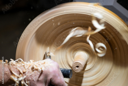 wood shavings in motion while turnery of a wooden bowl with chisel