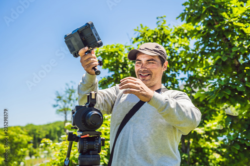 Photo sur Aluminium Noir a professional cameraman prepares a camera and a tripod before shooting