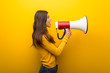 Leinwandbild Motiv Teenager girl on vibrant yellow background shouting through a megaphone to announce something in lateral position
