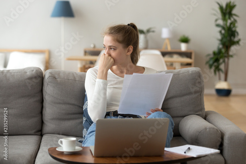 Fotografie, Obraz Unhappy young female sit on couch at home working at laptop reading paperwork, s